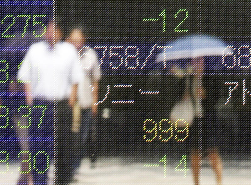 People are reflected on the electronic board of a securities firm in Tokyo, Monday, June 4, 2012. Asia stock markets took a beating Monday as signs that the U.S. economic recovery might be shifting into reverse sent investors fleeing. Japan's Nikkei 224 index dropped 2 percent to 8,269.14. (AP Photo/Koji Sasahara)