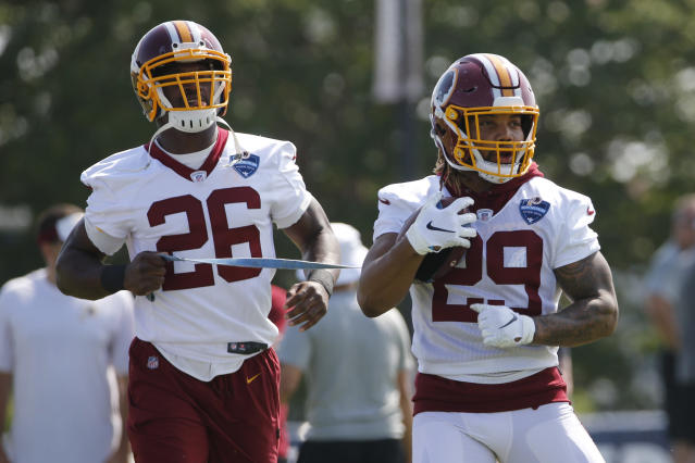 FILE - In this Friday, July 26, 2019, file photo, Washington Redskins running backs Derrius Guice (29) and Adrian Peterson (26) run drills during the NFL football training camp in Richmond, Va. Adrian Peterson told Derrius Guice to grab some ice cubes and wrap them around his surgically repaired left knee. Guice chuckled a bit. You're really old school, Guice said. We got all this Cryotherapy and stuff, and you're talking about bags of ice. Old school, meet new school in the Redskins backfield headlined by a 34-year-old climbing the all-time rushing list and a 22-year-old itching to make his NFL debut 13 months after a torn ACL. (AP Photo/Steve Helber, File)