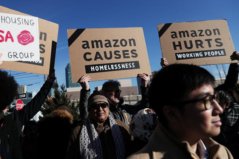 Demonstrators hold signs during a protest against Amazon in the Long Island City section of the Queens borough of New York, U.S., February 14, 2019. REUTERS/Shannon Stapleton
