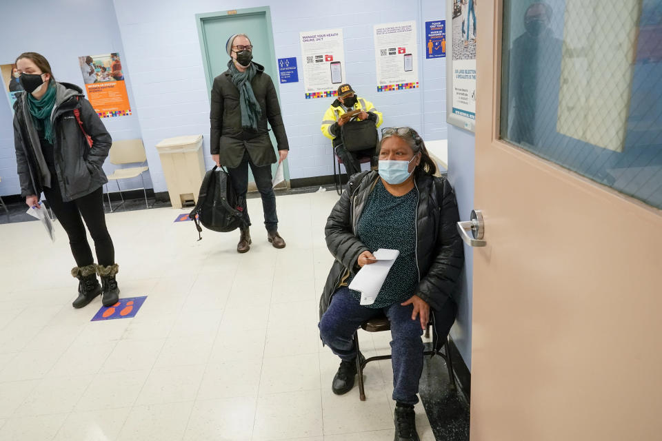 Maria Hernandez, right, of Manhattan, sits in a waiting area after registering for the first dose of the coronavirus vaccine at a COVID-19 vaccination site at NYC Health + Hospitals Metropolitan, Thursday, Feb. 18, 2021, in New York. (AP Photo/Mary Altaffer)