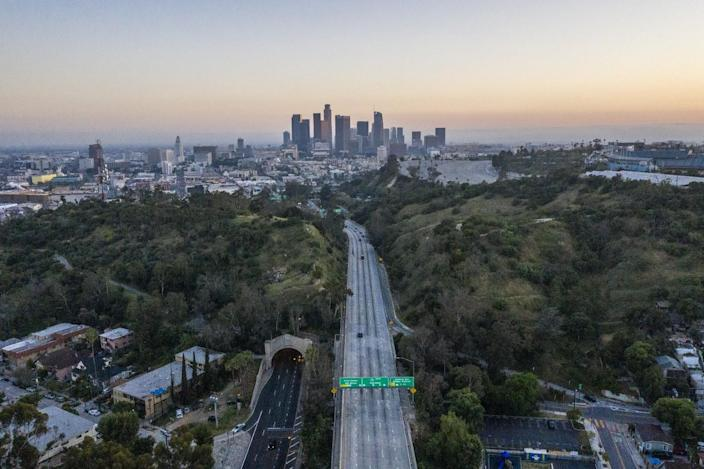Aerial view of a mostly empty freeway running between green hills toward the downtown L.A. skyline