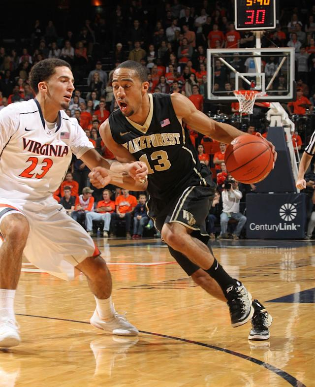 Wake Forest guard Coron Williams (13) drives past Virginia guard London Perrantes (23) during the first half of an NCAA college basketball game Wednesday, Jan. 8, 2014, in Charlottesville, Va. (AP Photo/Andrew Shurtleff)