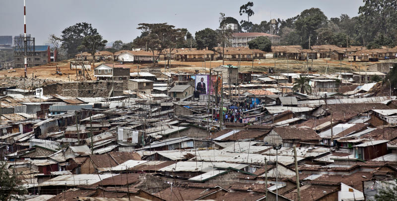 In this photo taken Tuesday, Feb. 26, 2013, an election campaigning poster hangs above tin-shack rooftops in the Mathare slum of Nairobi, Kenya. Kenya on Monday holds its first presidential election since its 2007 vote devolved into months of tribal violence, and in recent weeks in Nairobi's most dangerous slum Mathare dozens of tin shack homes have been burned to the ground and some families are moving into zones controlled by their own clans. (AP Photo/Ben Curtis)
