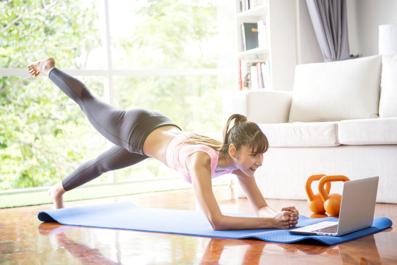 Healthy lifestyle and work life balance concepts. Young woman doing yoga excercise with online app on computer laptopn in her living room at home.