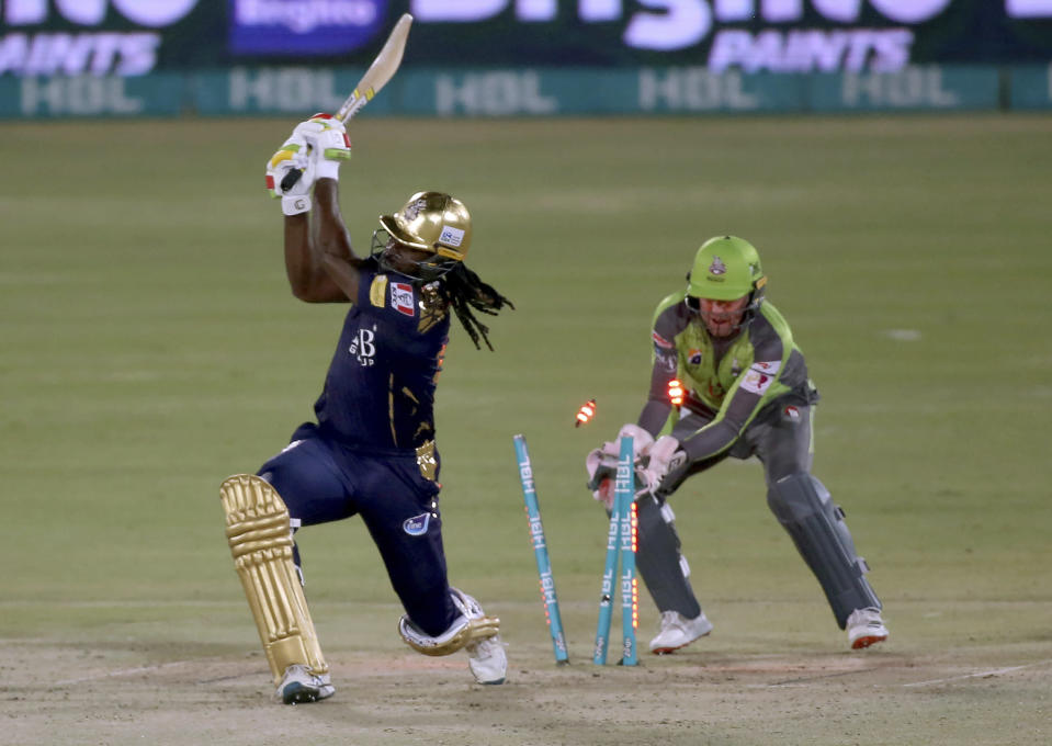Quetta Gladiators' Chris Gayle, left, is bowled out by Lahore Qalandars' Rashid Khan while teammate Ben Dunk watches during a Pakistan Super League T20 cricket match between Lahore Qalandars and Quetta Gladiators at the National Stadium, in Karachi, Pakistan, Monday, Feb. 22, 2021. (AP Photo/Fareed Khan)