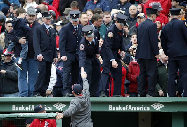Firefighters shake hands with Boston Red Sox's Jonny Gomes after being honored between innings of the home opener baseball game at Fenway Park In Boston, Friday, April 4, 2014 between the Red Sox and the Milwaukee Brewers. (AP Photo/Elise Amendola)