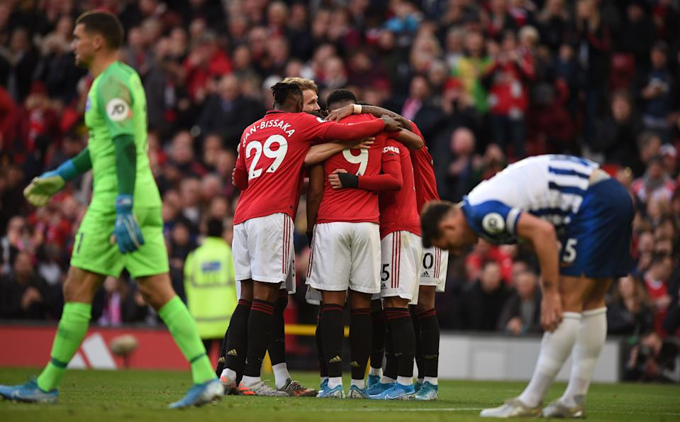 Manchester United players celebrate the opening goal scored by Manchester United's Belgian-born Brazilian midfielder Andreas Pereira during the English Premier League football match between Manchester United and Brighton and Hove Albion at Old Trafford in Manchester, north west England, on November 10, 2019. (Photo by Oli SCARFF / AFP) / RESTRICTED TO EDITORIAL USE. No use with unauthorized audio, video, data, fixture lists, club/league logos or 'live' services. Online in-match use limited to 120 images. An additional 40 images may be used in extra time. No video emulation. Social media in-match use limited to 120 images. An additional 40 images may be used in extra time. No use in betting publications, games or single club/league/player publications. /  (Photo by OLI SCARFF/AFP via Getty Images)