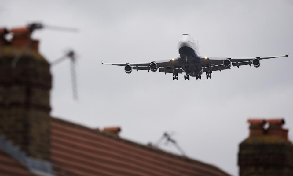 An aircraft flies over residential houses in Hounslow as it prepares to land at London Heathrow airport on December 5, 2015. British Prime Minister David Cameron's government is considering whether to approve a third runway at Heathrow or expand air capacity in southeast England at another airport such as London Gatwick. A decision is expected by the end of 2015.  AFP PHOTO / LEON NEAL / AFP PHOTO / Leon NEAL        (Photo credit should read LEON NEAL/AFP via Getty Images)