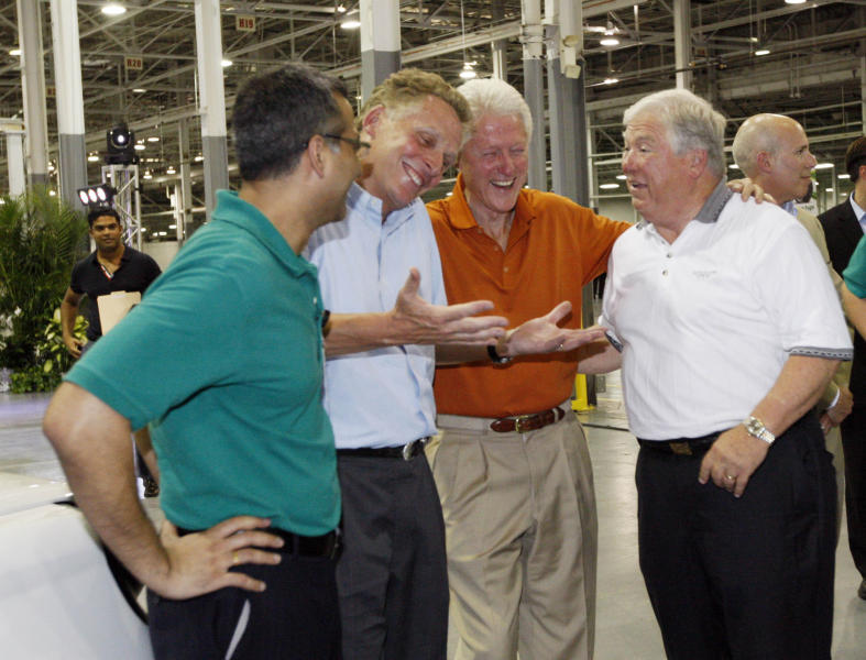 File-In this July 6, 2012, file photograph, then GreenTech Automotive executive Terry McAuliffe, second from left, jokes with former President Bill Clinton, center and former Mississippi Gov. Haley Barbour following the unveiling of their new electric MyCar at their manufacturing facility in Horn Lake, Miss. The big plans of eventually hiring a workforce of 25,000 people and eventually producing 1 million cars a year have been scaled back to a smaller facility to make 30,000 electric vehicles a year. (AP Photo/Rogelio V. Solis, File)