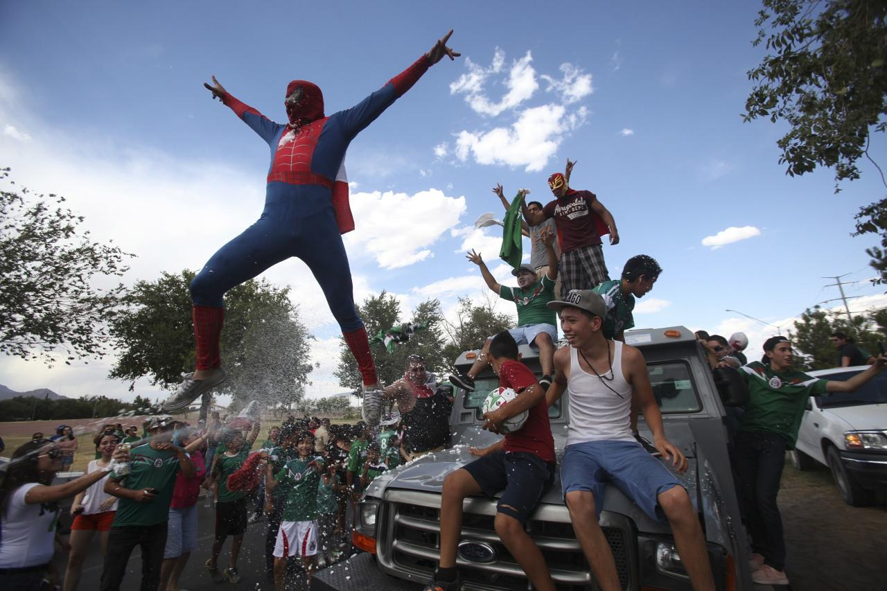 A Mexican soccer fan, dressed in a Spiderman costume, jumps from a vehicle as he celebrates Mexico's 2014 World Cup soccer match win over Croatia, in Ciudad Juarez June 23, 2014. REUTERS/Jose Luis Gonzalez (MEXICO - Tags: SPORT SOCCER WORLD CUP TPX IMAGES OF THE DAY)