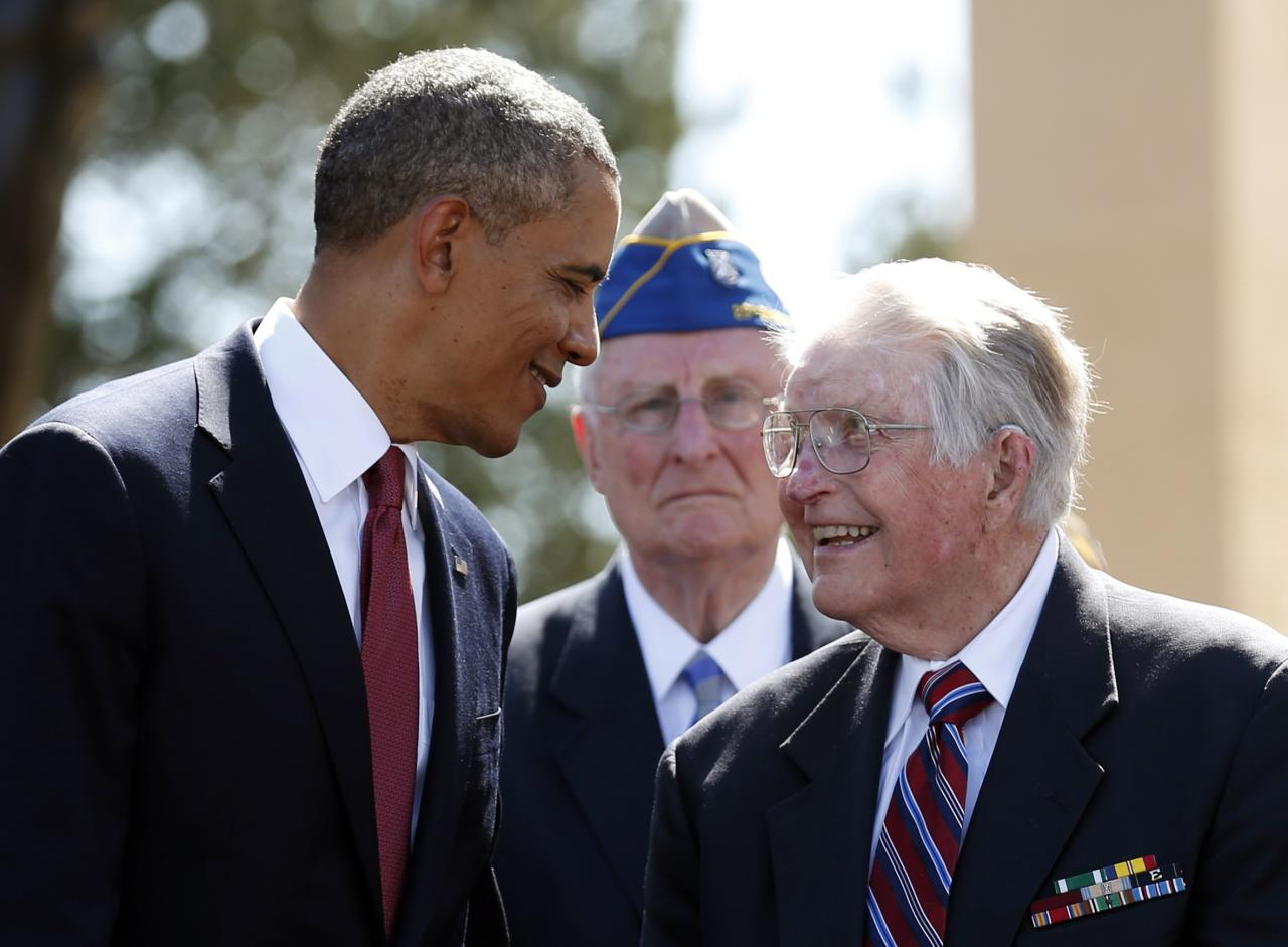 U.S. President Barack Obama (L) smiles at a veteran while during the 70th French-American Commemoration D-Day Ceremony at the Normandy American Cemetery and Memorial in Colleville-sur-Mer June 6, 2014. World leaders and veterans gathered by the beaches of Normandy under clear blue skies on Friday to mark the 70th anniversary of World War Two's D-Day landings, with host France hoping the event will help bring a thaw in the Ukraine crisis. REUTERS/Kevin Lamarque (FRANCE - Tags: POLITICS ANNIVERSARY CONFLICT)