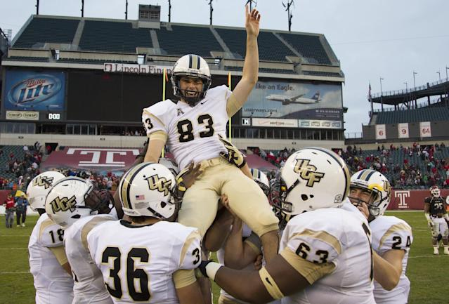 Teammates lift Central Florida kicker Shawn Moffitt (83) into the air after kicking the game-winning field goal late in the fourth quarter of an NCAA college football game against the Temple, Saturday, Nov. 16, 2013, in Philadelphia. Central Florida win 39-36. (AP Photo/Chris Szagola)