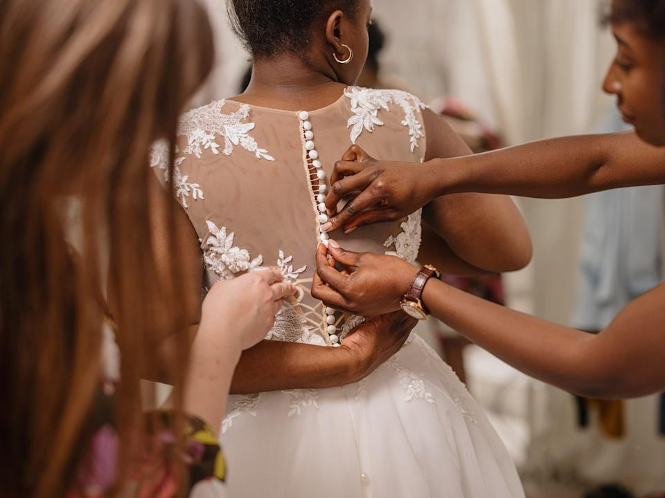 Woman trying on wedding dress with female friends having fun and helping her fit the dress - stock photo