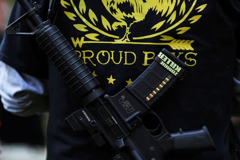 FILE PHOTO: A Proud Boy carries a gun during a gathering at a local park in Vancouver, Washington