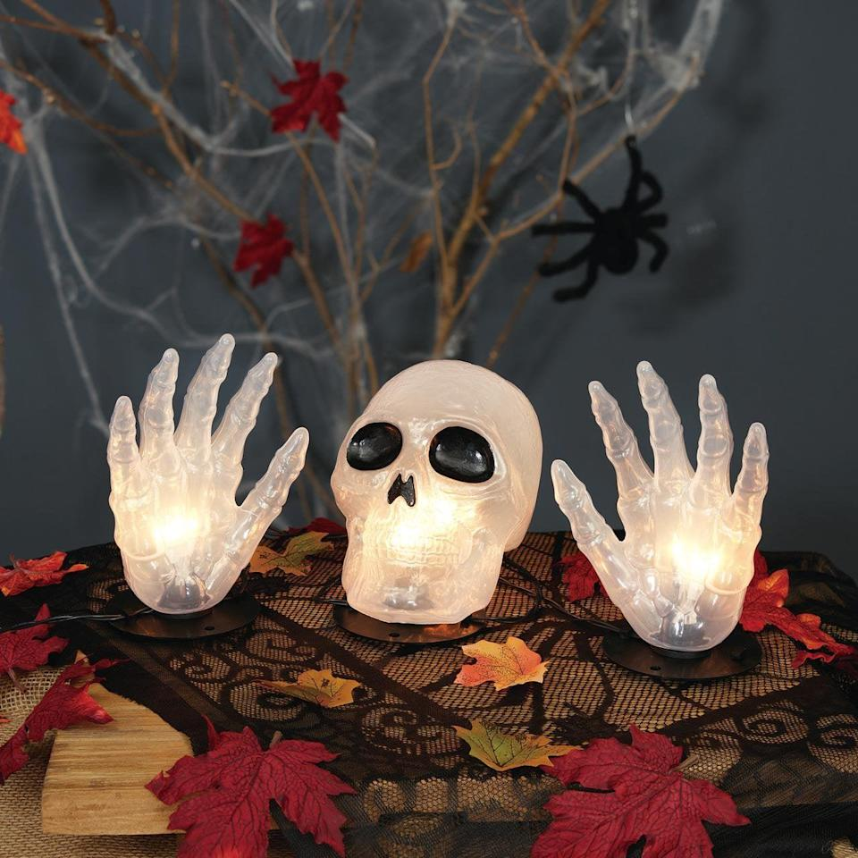 <p>Add this <span>Way to Celebrate Halloween 3-Piece Skull With Hands Light Set</span> ($10) to your tables, steps, lawn, and more. It lights up so you can use it day and night, indoors and outdoors.</p>