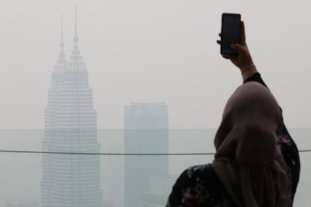 A tourist takes a picture of the city skyline shrouded by haze at Kuala Lumpur Tower in Kuala Lumpur