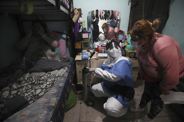 City worker Carlos Ruiz gives instruction to a family member after delivering a tank of oxygen for a COVID-19 patient, in her home in the Iztapalapa borough of Mexico City, Friday, Jan. 15, 2021. The city offers free oxygen refills for COVID-19 patients. (AP Photo/Marco Ugarte)