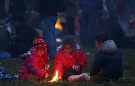 Migrants' children keep themselves warm around a fire after crossing the border from Croatia in Rigonce