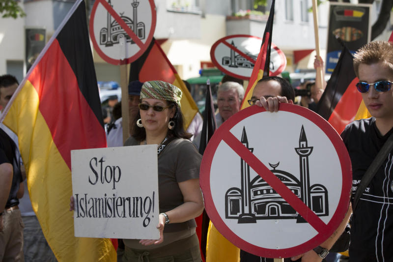 """Demonstrators display signs with crossed mosques during a protest in front of a mosque in Berlin, Germany, Saturday, Aug. 18, 2012. A Berlin court had allowed the demonstration of the far-right group ' Pro Deutschland' held under the slogan """"Islam does not belong in Germany — stop Islamization."""" (AP Photo/Gero Breloer)"""