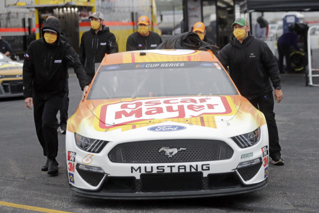 Crew members push the car of driver Ryan Newman as they wear masks as required for safety measures due to the coronavirus pandemic before the Toyota 500 NASCAR Cup Series auto race Wednesday, May 20, 2020, in Darlington, S.C. (AP Photo/Brynn Anderson)
