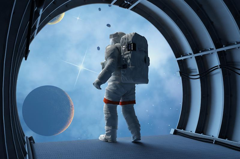 Astronaut peering through a space station window at the moon