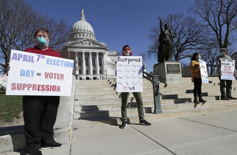 A group with C.O.V.I.D., Citizens Outraged Voters in Danger, including, from left, Ron Rosenberry Chase and Jim O'Donnell, protest while wearing masks outside the State Capitol during a special session regarding the spring election in Madison, Wis., Saturday, April 4, 2020. (Amber Arnold/Wisconsin State Journal via AP)