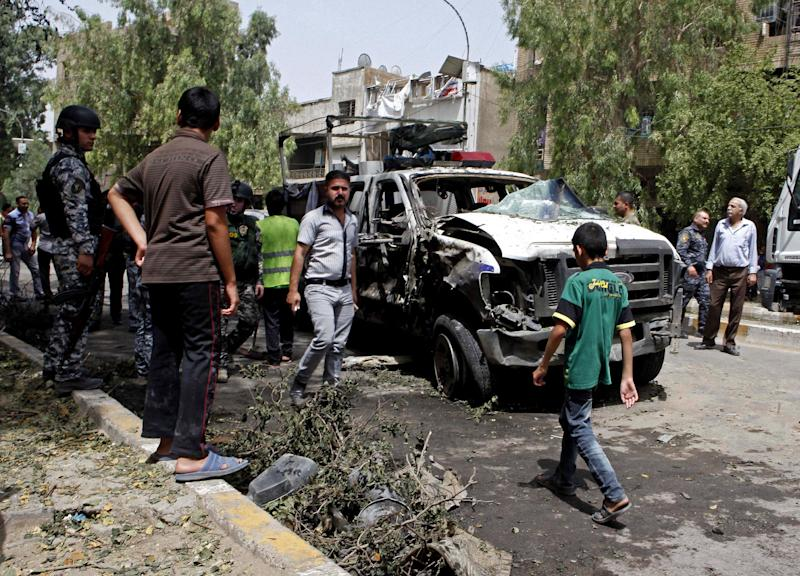 CAPTION CORRECTION, CORRECTS SECOND SENTENCE - Iraqis gather at the scene of a bomb attack in the commercial area of Karradah in Baghdad, Iraq, Thursday, May 30, 2013. A series of morning bomb explosions in Baghdad and the northern Iraqi city of Mosul on Thursday, killed and wounded dozens of people, police said, in the latest eruption of violence rattling the country. (AP Photo/Hadi Mizban)