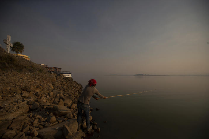 A man fishes off the banks of the Villa Victoria Dam, the main water supply for Mexico City residents, on the outskirts of Toluca, Mexico Thursday, April 22, 2021. Drought conditions now cover 85% of Mexico, and in areas around Mexico City and Michoacán, the problem has gotten so bad that lakes and reservoirs are drying up. (AP Photo/Fernando Llano)