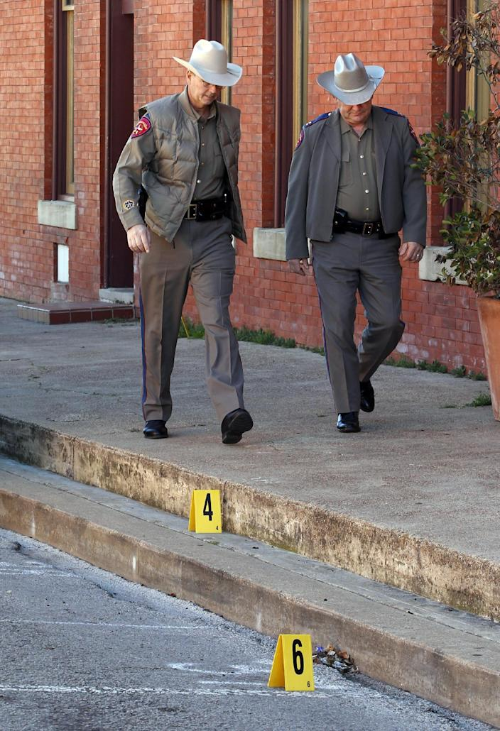 Law enforcement officers walk past some evidence markers that were placed on Grove Street after an assistant District Attorney was shot and killed on Thursday, Jan. 31, 2013 in downtown Kaufman, Texas. Kaufman County Assistant District Attorney Mark Hasse was shot and killed early Thursday morning as he was walking from his car to the courthouse. (AP Photo/The Dallas Morning News, David Woo) MANDATORY CREDIT; NO SALES; MAGS OUT; TV OUT; INTERNET USE BY AP MEMBERS ONLY