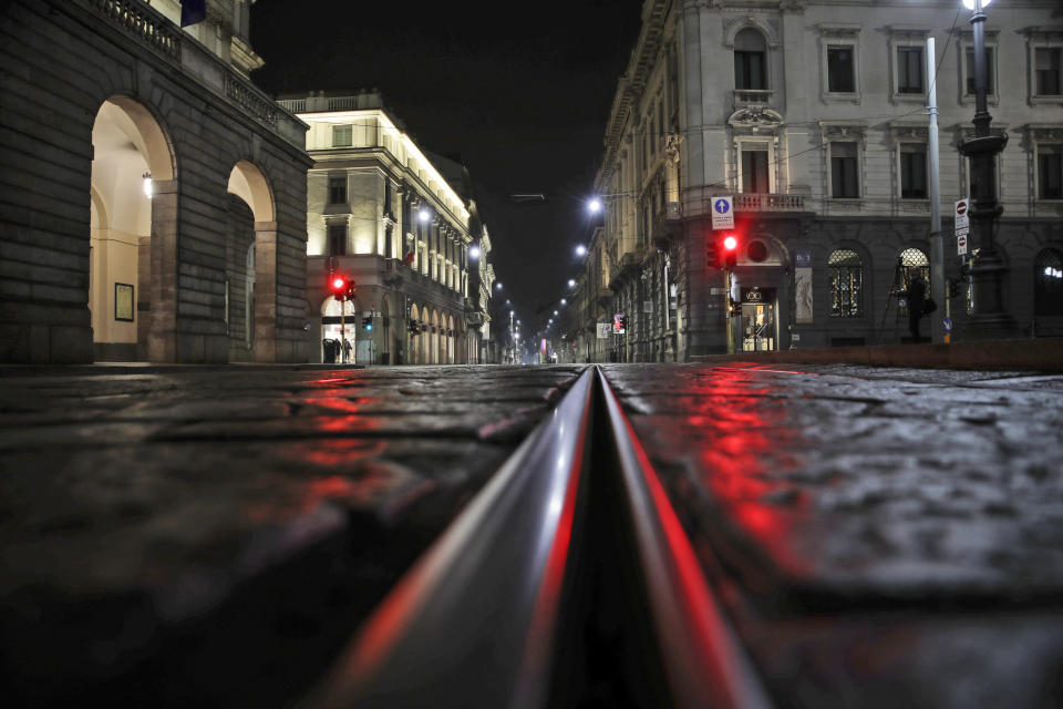 An empty street in front of La Scala opera house is lit by a red traffic light in Milan, northern Italy, early Sunday, Oct. 25, 2020. Since the 11 p.m.-5 a.m. curfew took effect last Thursday, people can only move around during those hours for reasons of work, health or necessity. (AP Photo/Luca Bruno)
