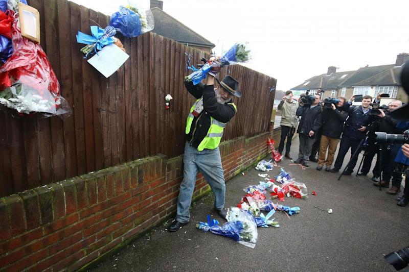 Iain Gordon pulls the flowers down from a fence opposite the house (PA)