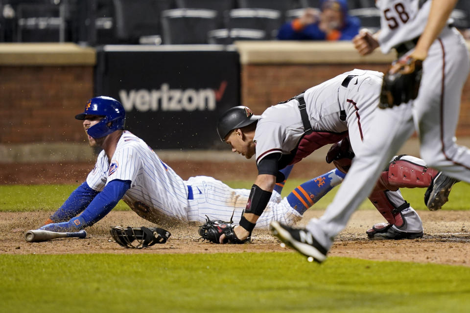 New York Mets' Pete Alonso looks up after scoring the game-winning run against Arizona Diamondbacks catcher Carson Kelly, center, during the 10th inning of a baseball game Friday, May 7, 2021, in New York. (AP Photo/John Minchillo)