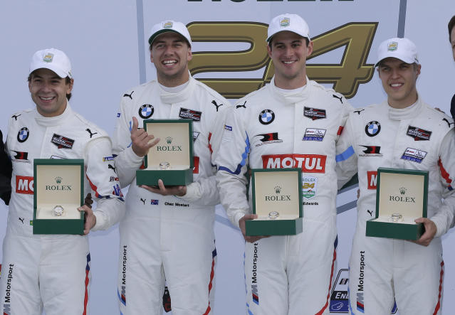 GT Le Mans class winners Augusto Farfus, Chaz Mostert, John Edwards and Jesse Krohn hold their Rolex watches in Victory Lane after the Rolex 24-hour auto race at Daytona International Speedway, Sunday, Jan. 26, 2020, in Daytona Beach, Fla. (AP Photo/Terry Renna)