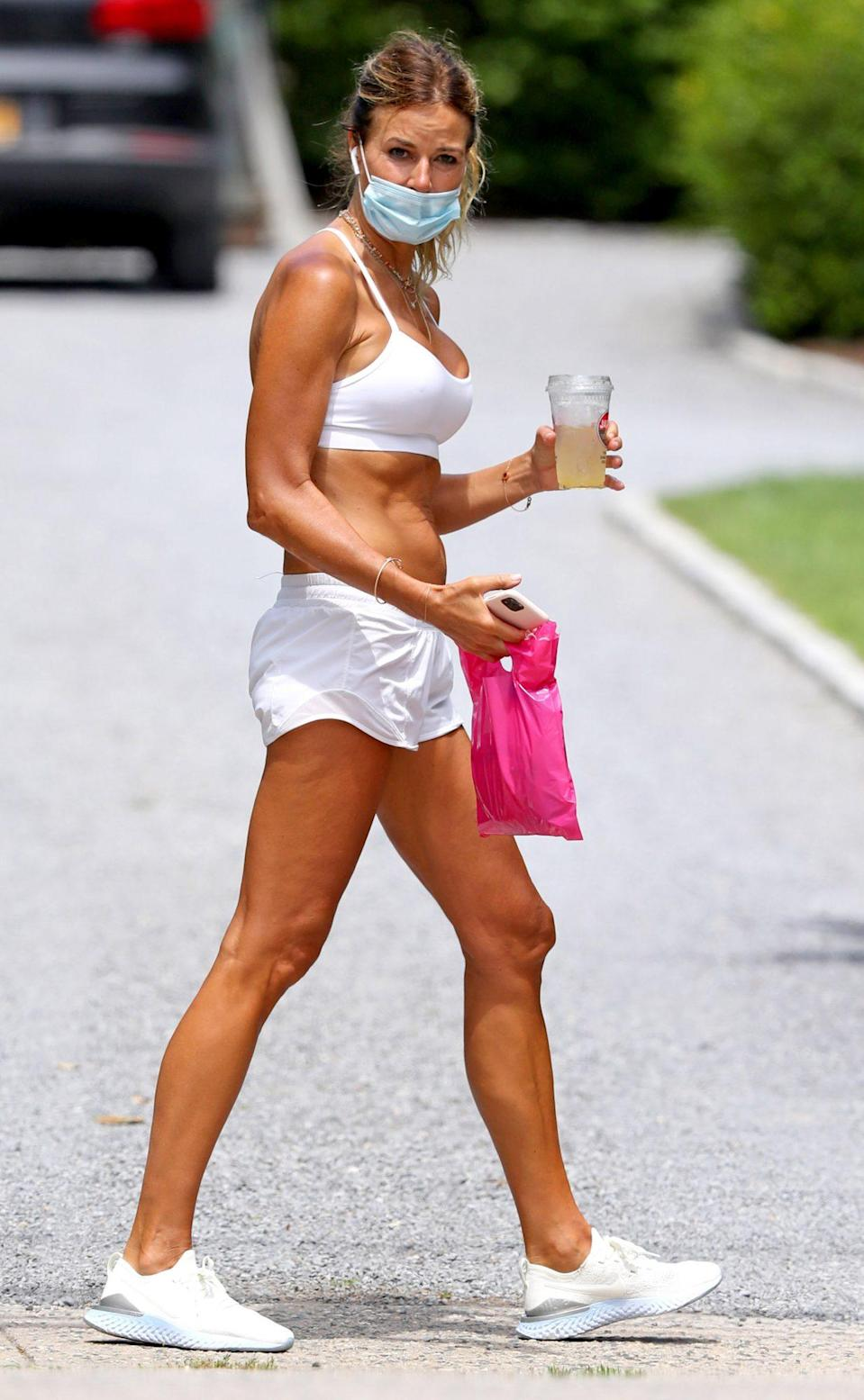 <p>Kelly Bensimon grabs her drink to-go in The Hamptons, New York, on Monday.</p>