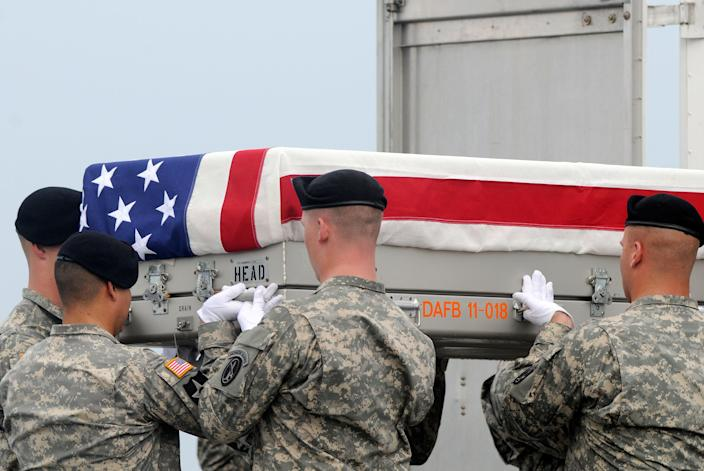 An Army carry team lifts a transfer case containing the remains of Staff Sgt. Richard L. Berry Tuesday, July 24, 2012 at Dover Air Force Base, Del. According to the Department of Defense, Berry, 27, of Scottsdale, Ariz., died July 22, 2012 in Kandahar, Afghanistan of wounds from an improvised explosive device. (AP Photo/Steve Ruark)