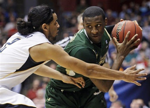 South Florida guard Jawanza Poland is pressured by California guard Jorge Gutierrez (2) in the first half of an NCAA tournament first-round college basketball game, Wednesday, March 14, 2012, in Dayton, Ohio. (AP Photo/Al Behrman)