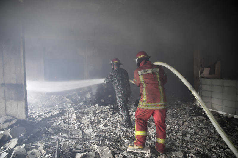 Lebanese firemen extinguish a fire inside a building that was burned in a wildfire overnight, in the town of Damour just over 15km (9 miles) south of Beirut, Lebanon, Tuesday, Oct. 15, 2019. Strong fires spread in different parts of Lebanon forcing some residents to flee their homes in the middle of the night as the flames reached residential areas in villages south of Beirut. (AP Photo/Hassan Ammar)