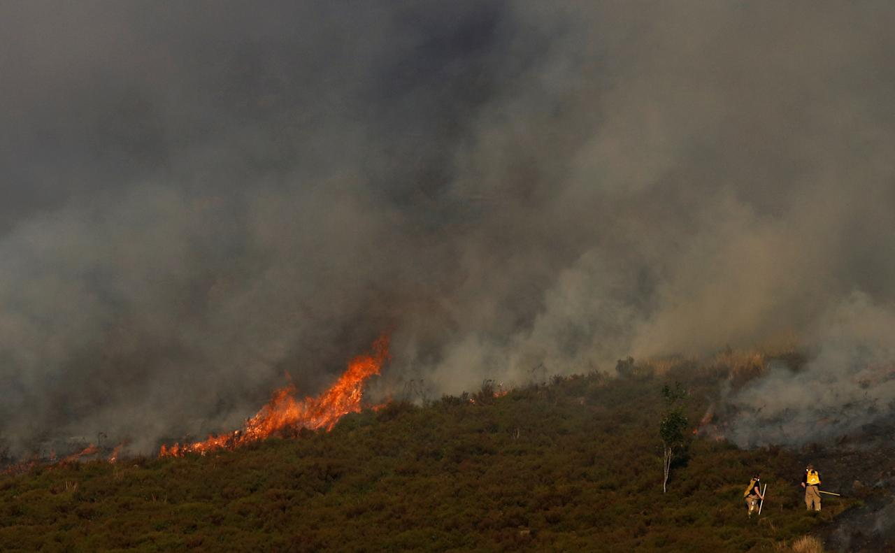 <p>Firefighters tackle a blaze on Saddleworth Moor (Reuters/Phil Noble) </p>