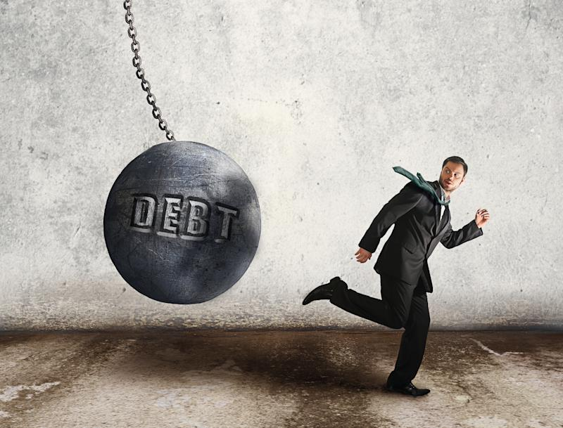 Businessman running from a giant ball on a chain with the word debt engraved on it