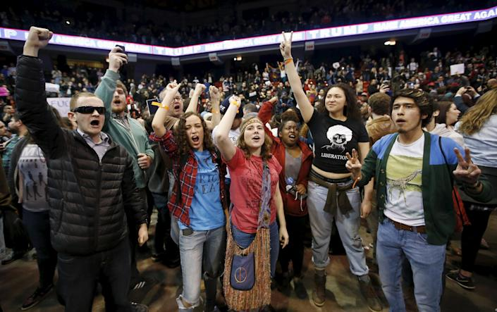 Demonstrators celebrate after Republican U.S. presidential candidate Donald Trump cancelled his rally at the University of Illinois at Chicago March 11, 2016. (REUTERS/Kamil Krzaczynski)