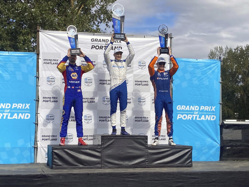 Alex Palou, center, celebrates his third IndyCar win of the season on Sunday, Sept. 12, 2021 at Portland International Raceway in Portland, Ore. Palou's win moved him back atop the IndyCar championship standings with two races remaining. Alexander Rossi finished second and Scott Dixon, teammates with Palou at Chip Ganassi Racing, finished third. (AP Photo/Jenna Fryer)