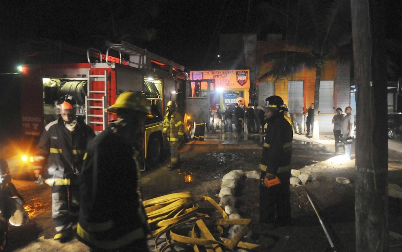 Firefighters stand outside of the prison in Comayagua, Honduras, a town 90 miles (140 kilometers) north of the Central American country's capital, Tegucigalpa, early Wednesday, Feb. 15, 2012. Radio reports from Comayagua said dozens of prisoners were burned beyond recognition and the prison was destroyed by the flames. The fire claimed the lives of at least 272 inmates. (AP Photo/Fernando Antonio)