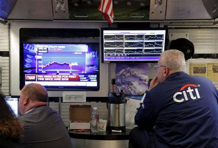 FILE PHOTO - Traders work on the floor of the New York Stock Exchange (NYSE) shortly after the announcement that the U.S. Federal Reserve had hiked interest rates for the first time in nearly a decade in New York, U.S., on December 16, 2015.  REUTERS/Lucas Jackson/File Photo