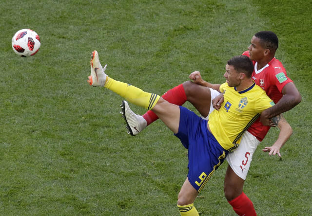 <p>Sweden's Marcus Berg, left, duels for the ball with Switzerland's Manuel Akanji during the round of 16 match between Switzerland and Sweden at the 2018 soccer World Cup in the St. Petersburg Stadium, in St. Petersburg, Russia, Tuesday, July 3, 2018. (AP Photo/Dmitri Lovetsky) </p>