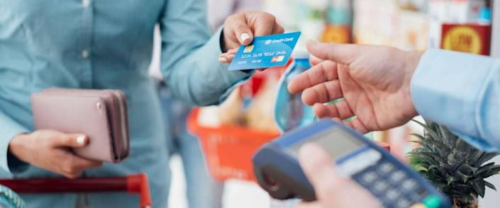 Woman at the supermarket checkout, she is paying using a credit card, shopping and retail concept