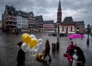 A bridal couple and friends walk over the Roemerberg square after their wedding in Frankfurt, Germany, Thursday, Jan. 28, 2021. Further restrictions to avoid the outspread of the coronavirus are discussed Thursday by the German government. (AP Photo/Michael Probst)