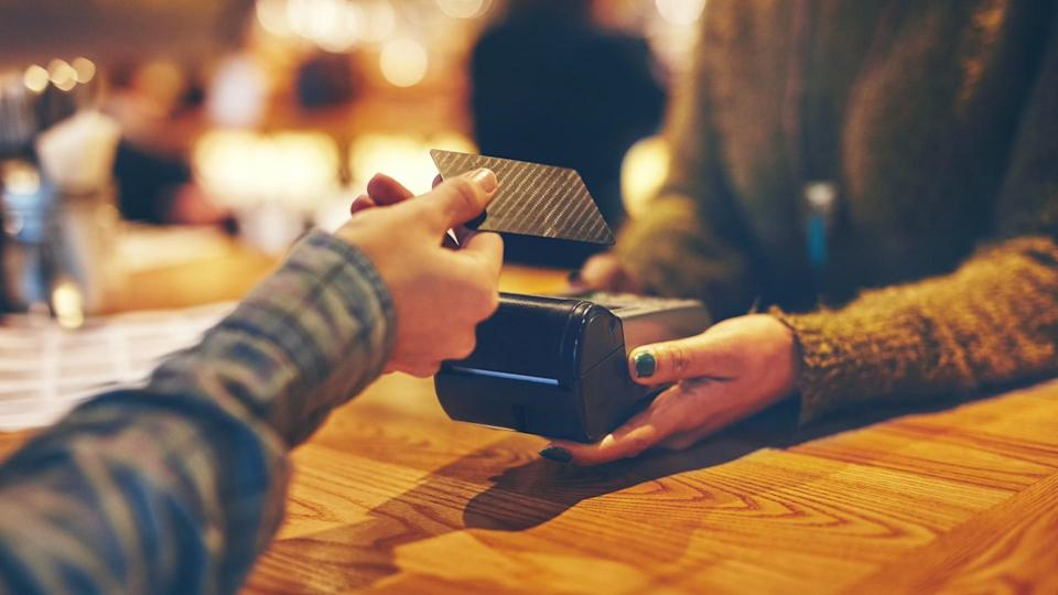 Closeup shot of a customer making a credit card payment in a cafe.