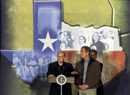 U.S. President George W. Bush (R) looks on as Russian President Vladimir Putin makes remarks at the Crawford High School in Crawford, Texas, in this November 15, 2001 file photo. REUTERS/Jeff Mitchell/Files