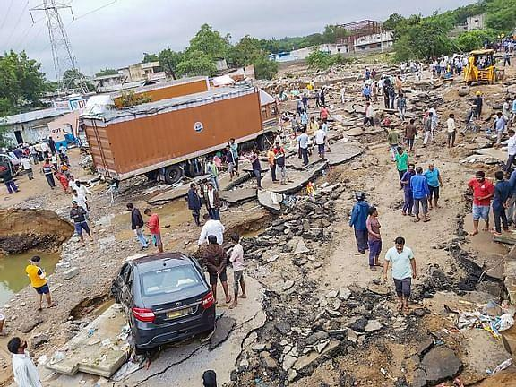 People gather after a road caved-in following incessant rainfall across the state, at Gaganpahad-Shamshabad Road near Hyderabad, Wednesday, Oct. 14, 2020.
