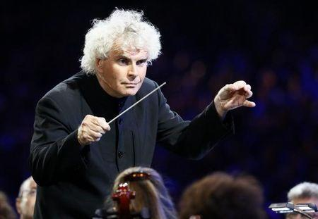 Conductor Simon Rattle takes part in the opening ceremony of the London 2012 Olympic Games at the Olympic Stadium July 27, 2012. REUTERS/Kai Pfaffenbach/Files